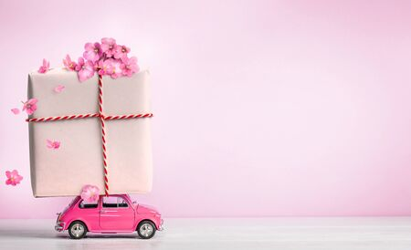 Pink toy car with gift box on a roof and flowers on pink background. Copy space.