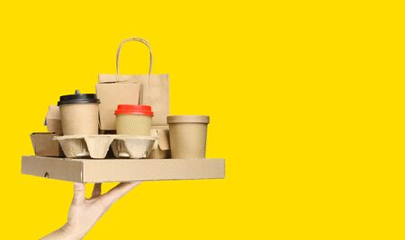 Hand holding various take-out food containers, pizza box, coffee cups in holder and paper bag on yellow background. Food delivery service