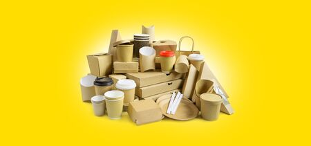 Many Various take-out food containers, pizza box, coffee cups in holder and paper boxes on yellow background.