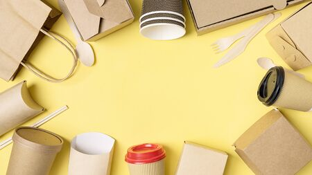 Various Fast food packaging set on yellow background. Food delivery service. Top view. Copy space.