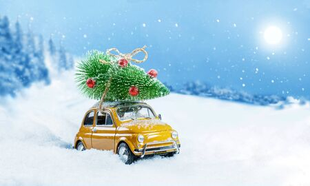Retro toy no name car carrying christmas tree on roof in snowy winter forest. Christmas background. Holidays card. Copy space.