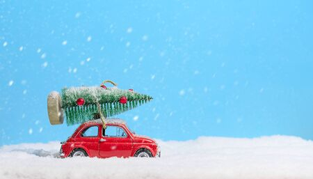 Retro red toy car carrying christmas tree on roof in the snow on blue background. Christmas background. Holidays card. Copy space.