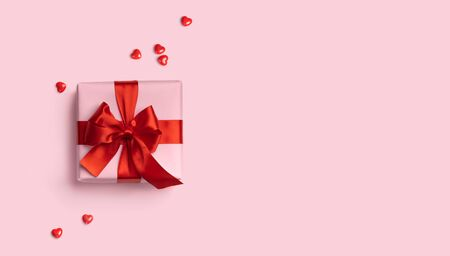 Pink gift box with red bow on pink background with red hearts around. Holiday web banner. Top view. Flat lay. Copy space Imagens