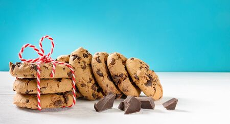 Chocolate chip cookies stack on white wooden table and blue background. Copy space