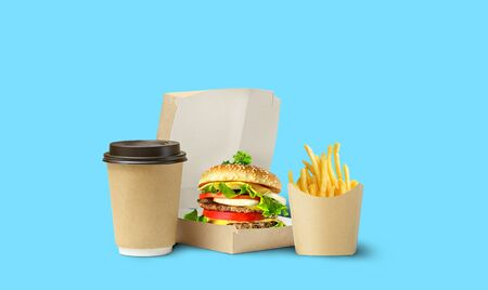 Fast food lunch delivery. Tasty Hamburger, fries and coffee in cardboard package on blue background.