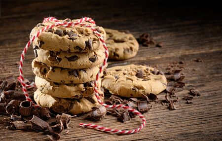 Chocolate chip cookies stack tied with a red rope on wooden rustic table