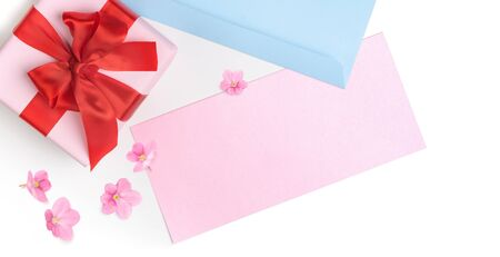 Pink gift box with red bow and blank greeting card for Valentine's day, love letter or wedding invitation. Top view. White background.