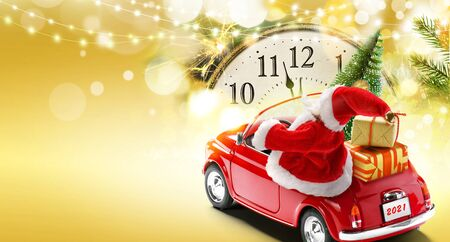 New Years Eve 2021 card background. Santa Claus driving red car with gift boxes and Christmas tree on golden background with bokeh lights
