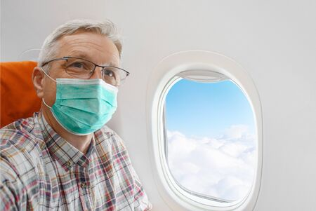 Man wearing mask in aircraft cabin, plane window with cloud sky. Prevention during Coronavirus COVID-19 pandemic