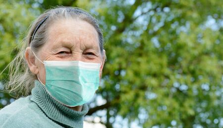 Portrait of smiling senior woman wearing medical mask outdoors in village. Prevention during Coronavirus COVID-19 pandemic