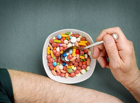 Person eats pills, tablets, capsules from a bowl with a spoon at the dinner table. Top view.