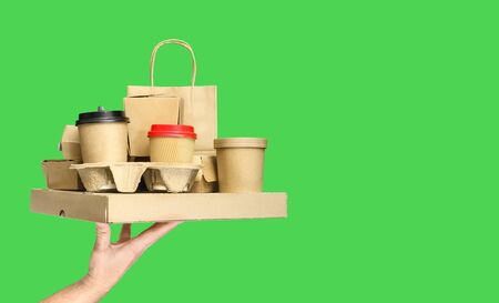 Hand holding various take-out food containers, pizza box, coffee cups in holder and paper bag on green background. Food delivery service