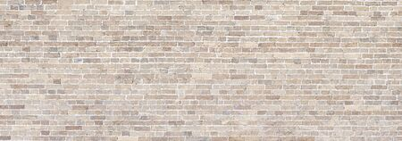 Wide Beige brick wall panoramic background or texture. Banco de Imagens