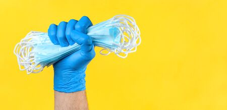 Hand in medical latex gloves holding heap of face protective masks. Protection against coronavirus COVID-19. Copy space