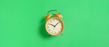 Orange vintage alarm clock on green background. Top view. Flat lay, copy space Imagens