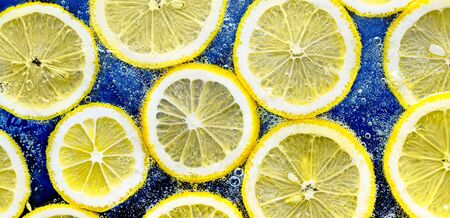 Lemon Slices in the water with air bubbles on blue background.