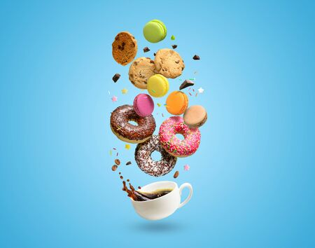 Pastries, confectionery flying over coffee cup with splash. Sweetshop and coffeeshop concept background. Copy space. Reklamní fotografie