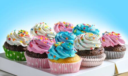Tasty Cupcakes packaging in delivery box, various cupcakes with pink white and blue cream and colorful sprinkles on blue background