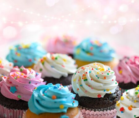 Festive delicious Cupcakes for party, birthday. Various cupcakes with pink white and blue cream on pink background. Copy space