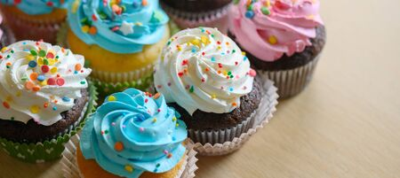 Festive delicious Cupcakes for party, birthday. Various cupcakes with pink white and blue cream on the table. Imagens