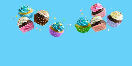 Cupcakes with pink white and blue cream and colorful sprinkles flying over blue background. Copy space