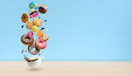 Donuts, cupcakes, cookies, macaroons and coffee cup flying over blue background. . Sweetshop and coffeeshop concept background. Copy space. Reklamní fotografie