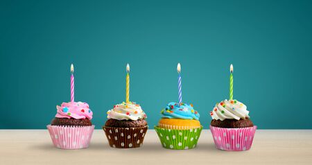 Row of colorful birthday cupcakes with burning candles on the table. Copy space Reklamní fotografie