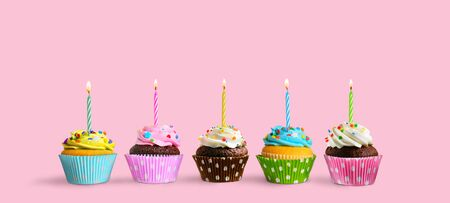 Row of colorful birthday cupcakes with burning candles on a pink background. Copy space Reklamní fotografie