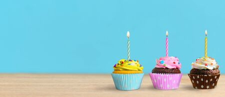 Birthday cupcakes with burning candles on the table and blue wall background