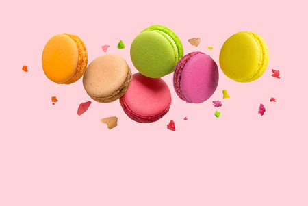French macaroons cookies falls mixed with crumbs on pink background. Copy space. Flat lay, top view. Reklamní fotografie