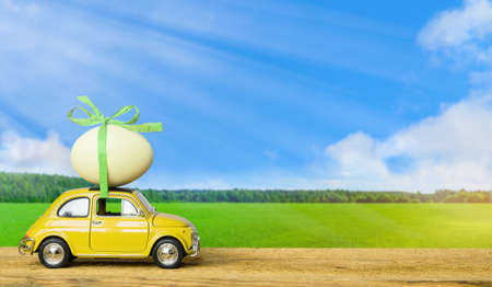 Retro toy car carrying an easter egg on the roof on green field and blue sky landscape background. Easter concept.
