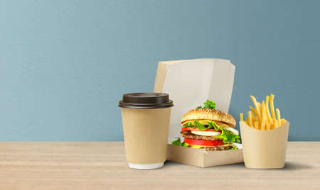 Tasty Hamburger, french fries and coffee in cardboard takeaway packaging. Copy space