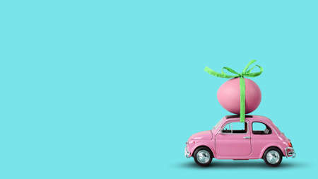 Pink retro toy car carrying an easter egg on the roof on a mint cyan background. Copy space
