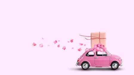 Pink retro car with gift box on a roof with flowers on pink background.