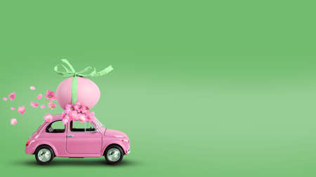 Pink retro toy car carrying an easter egg on the roof on a green background. Copy space Reklamní fotografie
