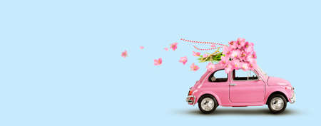 Pink retro toy car with bouquet of flowers on a roof on blue background. Flowers fast delivery