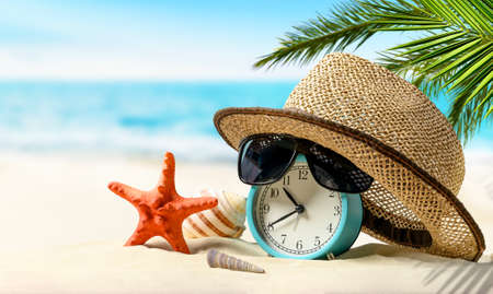 Summertime vacation concept. Time to relax. Alarm clock with straw hat, starfish on the sand beach and sea background.