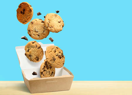 Chocolate chip cookies falling in paper box over aqua blue background.