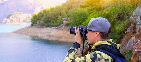 Boy photographer holding digital camera and shooting landscape of lake in the mountains