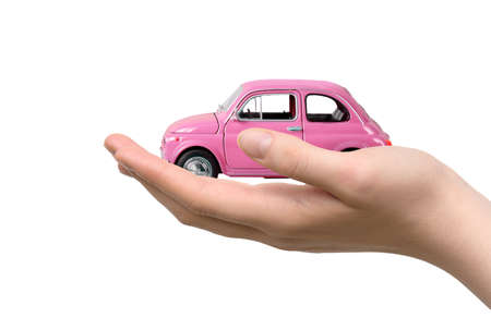 Pink toy car in woman hand on a white background. Car purchase concept