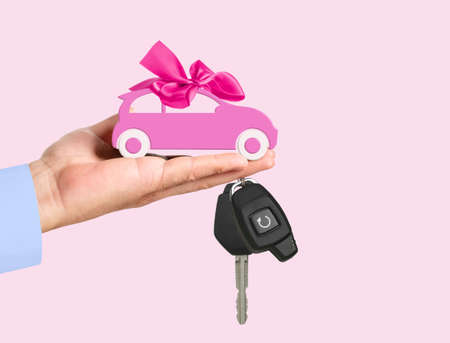 Car with bow and key on dealers palm isolated on a pink background. 版權商用圖片 - 152415170