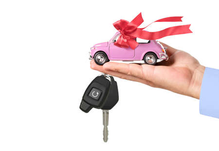 Pink Car with bow and key on dealers hand isolated on white background. Car purchase concept
