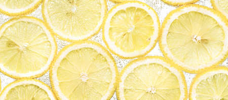 Slices of lemon in water with air bubbles background