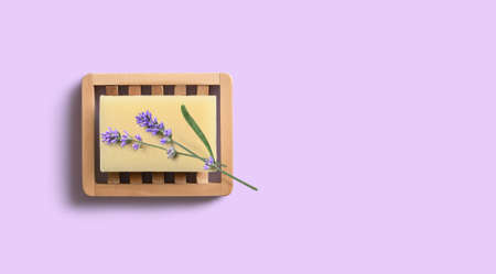 Natural homemade lavender soap with lavender flowers on wooden soap dish on purple background.