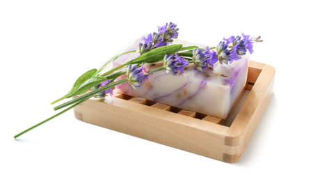 Natural homemade lavender soap with lavender flowers on wooden soap dish on white background. 版權商用圖片