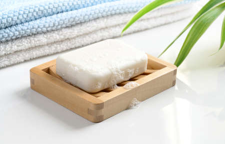 White Soap bar with foam on wooden soap dish and cotton towels on white table.