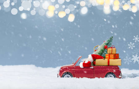 Santa Claus in Red car delivering christmas tree and presents at snowy background. Christmas background. 版權商用圖片