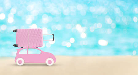 Pink toy car with pink suitcase on a roof on blue turquoise sea background