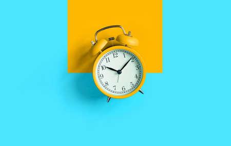 Orange vintage alarm clock on aqua blue background. Top view. Flat lay
