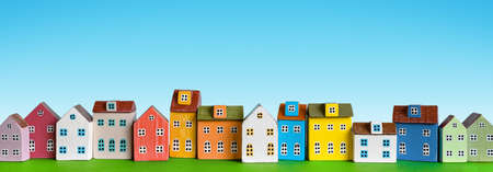 Colorful miniature houses arranged in a row on blue background. Urban city background banner. Copy space